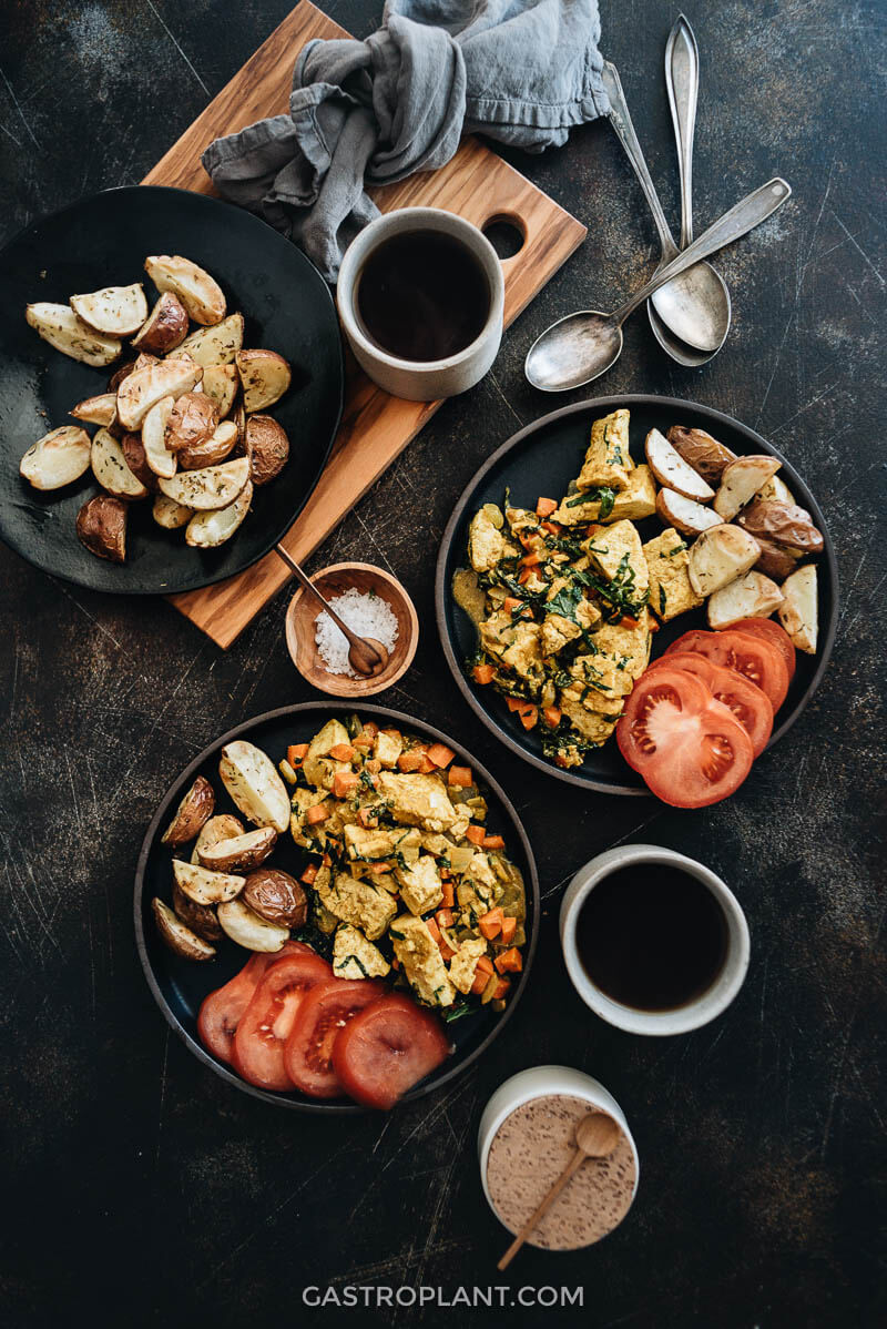 Curry tofu scramble on plates with roasted potatoes and tomatoes
