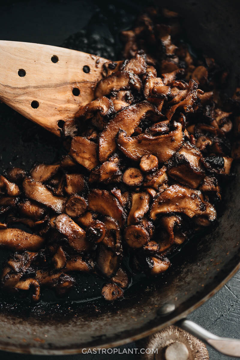 Vegan shiitake mushroom bacon in a sizzling skillet close-up