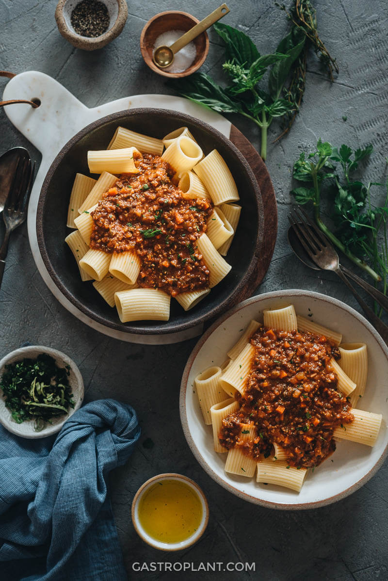 Two bowls of pasta topped with vegan bolognese