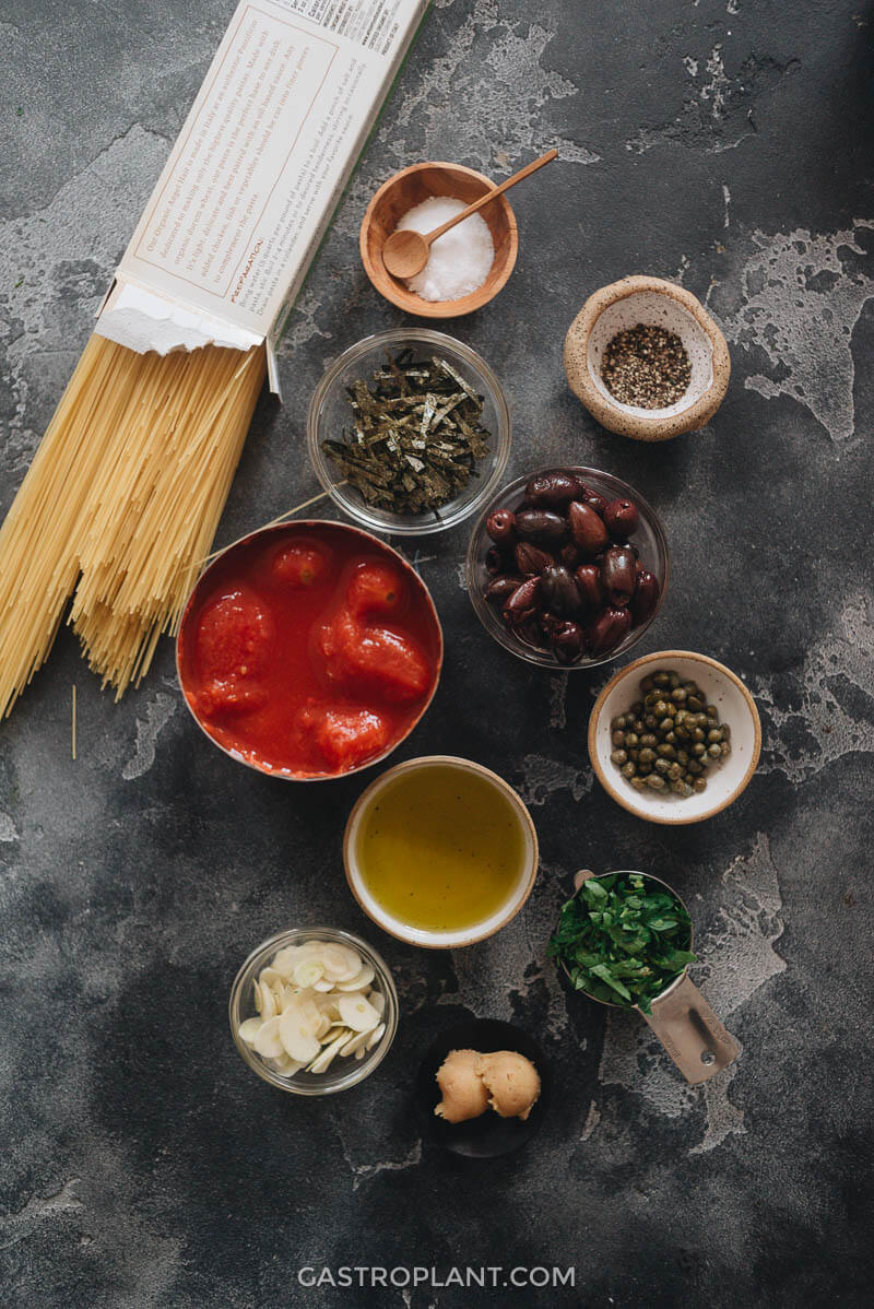 Ingredients for vegan puttanesca: pasta, tomatoes, olives, olive oil, garlic, capers, nori, miso, and parsley