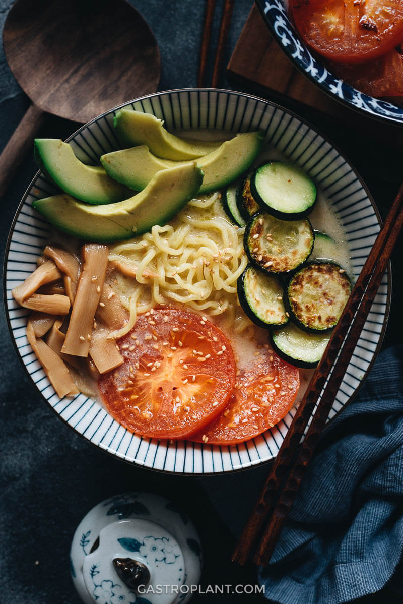 Homemade vegan ramen with tomato, zucchini, avocado, and menma