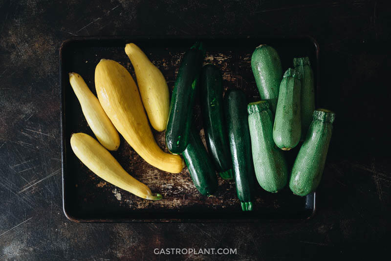 Fresh yellow, gray, and zucchini squash on a metal tray