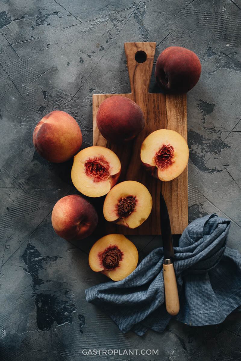 Raw cut peaches on cutting board