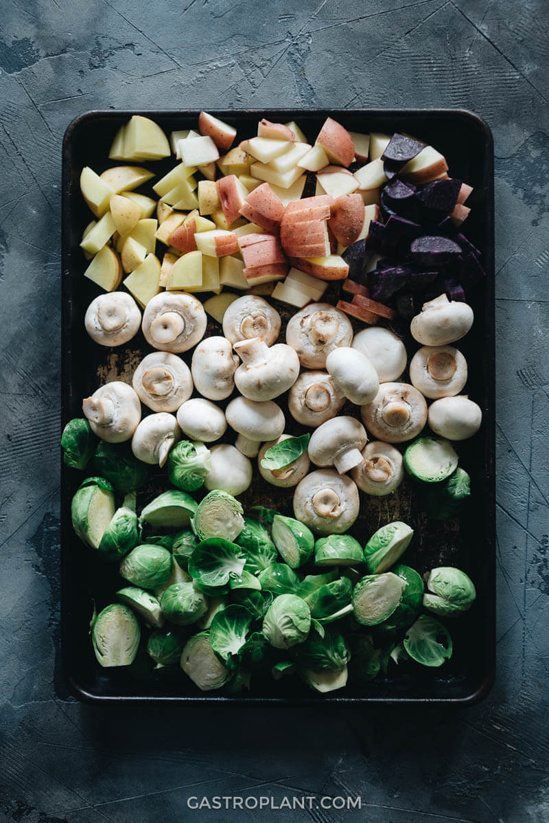 Raw brussels sprouts, potatoes, and mushrooms on a baking tray