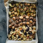 Roasted potatoes, mushrooms, and brussels sprouts on a sheet pan with parchmen