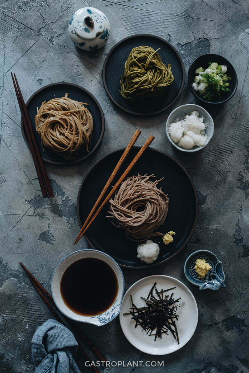 Vegan zaru soba with cold tsuyu sauce on table with daikon and ginger