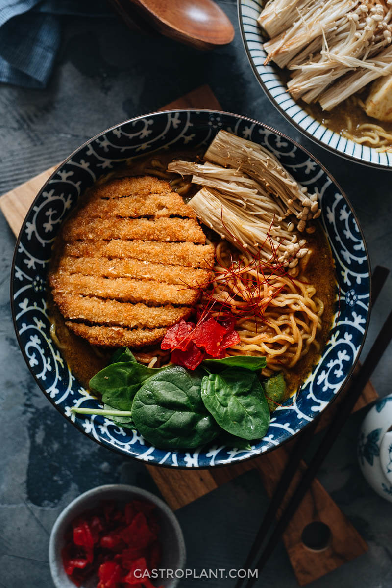 A bowl of vegan curry ramen noodle soup with vegan katsu on top