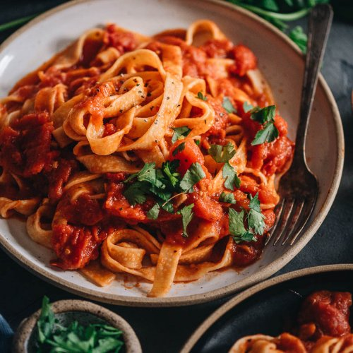 Marinara tagliatelle on a plate with fresh herbs