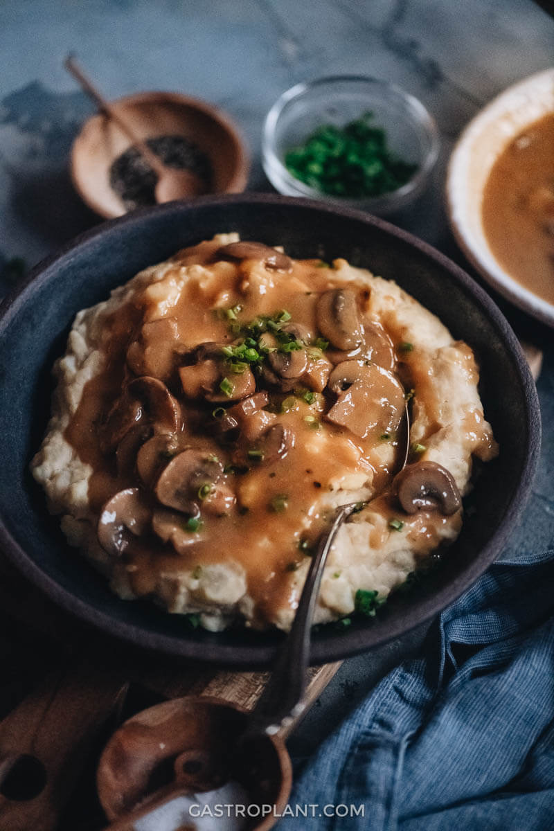 A bowl of mashed potatoes topped with vegan brown mushroom gravy