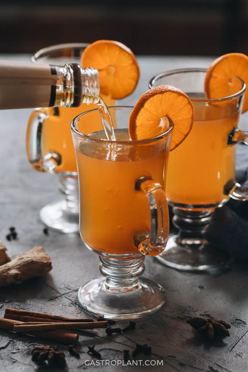 Pouring bourbon into a glass of mulled apple cider
