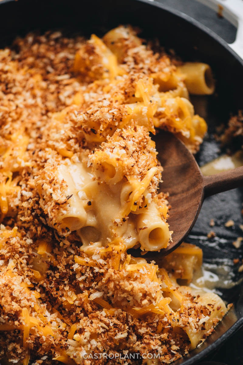 Cheesy vegan noodles topped with breadcrumbs being scooped with a wooden spoon