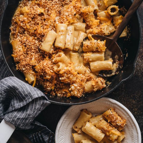 Creamy baked vegan mac and cheese in a skillet and bowl