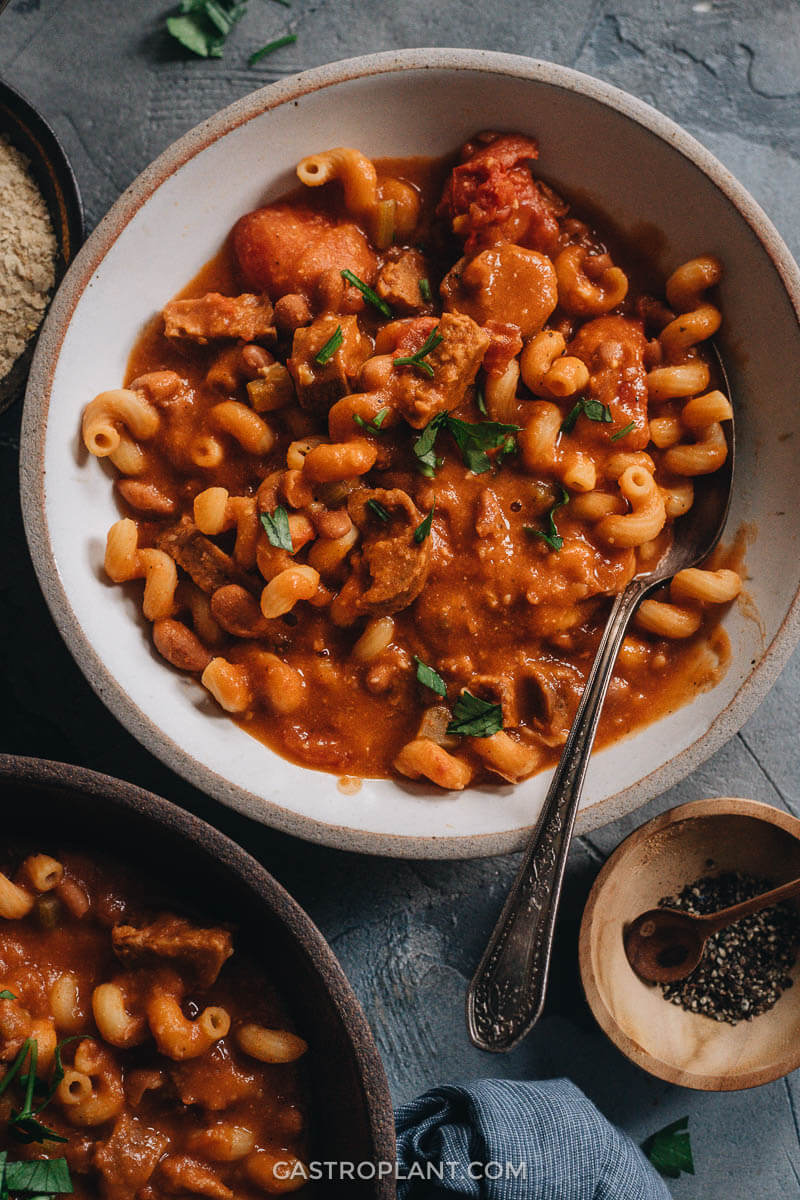 A white bowl with easy vegan tomato pasta e fagioli soup