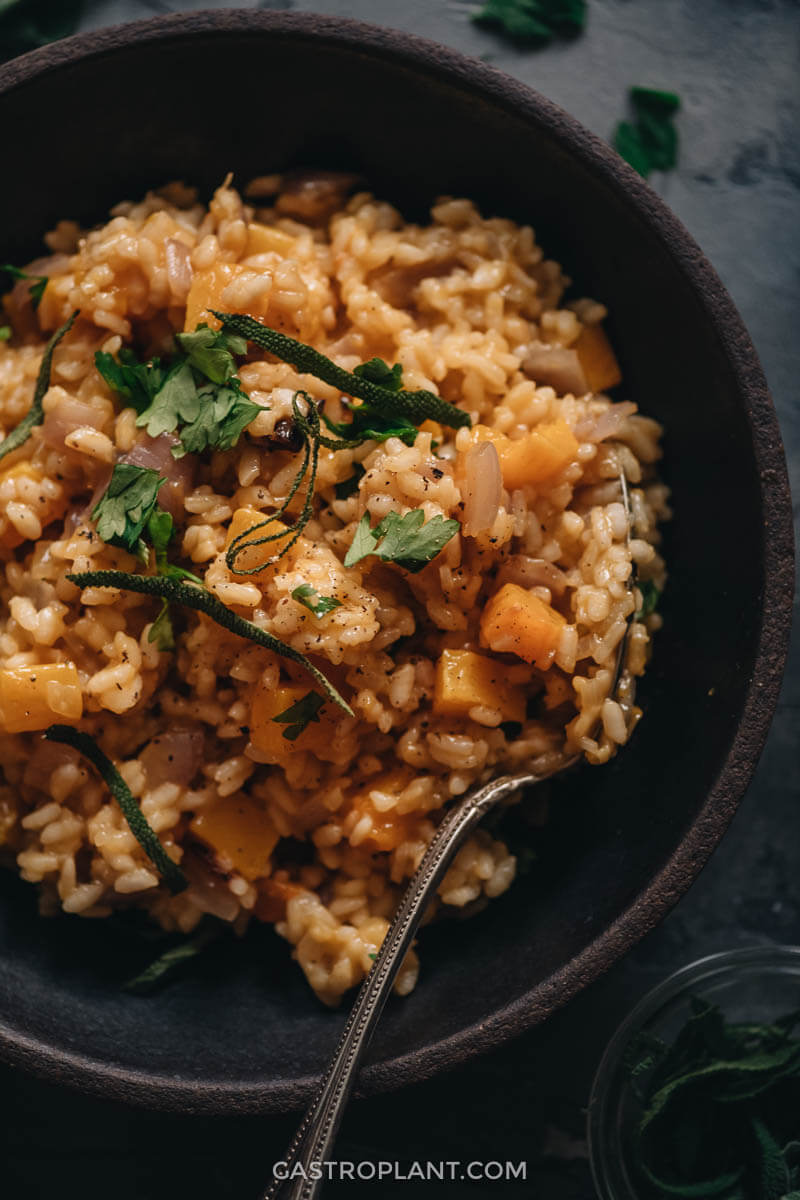A close up shot of vegan butternut squash risotto seasoned wit nutmeg and sage