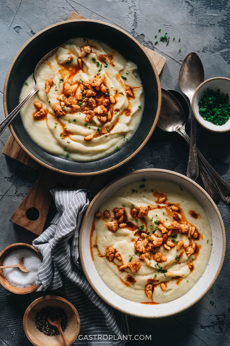 Two bowls of creamy vegan cauliflower soup with red paprika drizzle