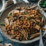 A bowl of fried rice with lots of mushrooms and a spoon