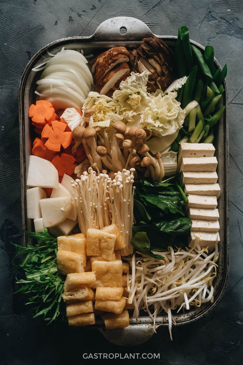 A tray full of mushrooms, tofu, aburaage, and vegetables for hot pot