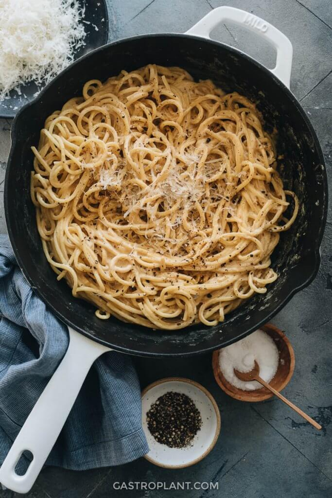 Vegan cacio e pepe pasta in a skillet with grated vegan parmesan