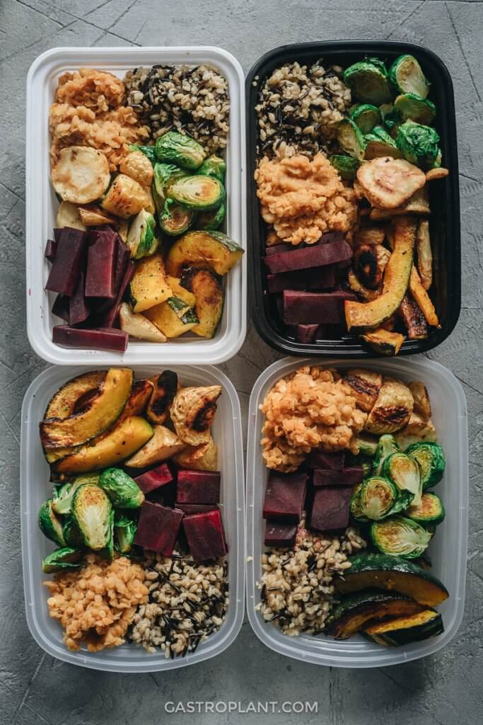 Four meal prep containers packed with vegan lunches