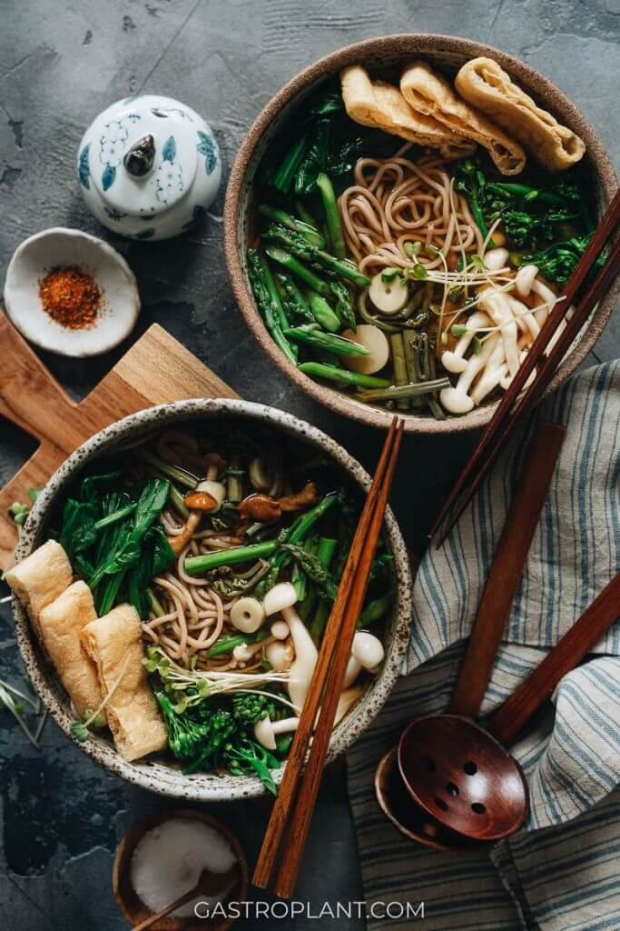 Two bowls of vegan sansai soba noodle soup with fresh spring vegetables