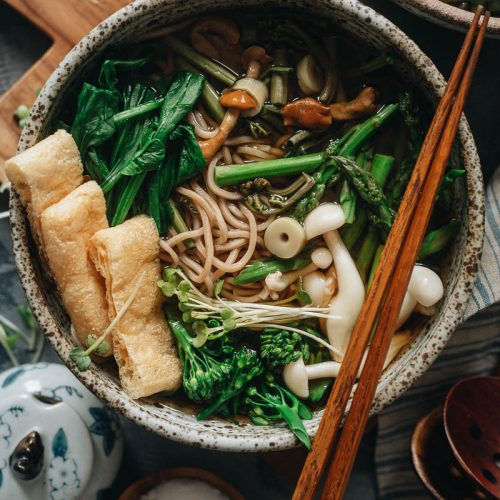 A bowl of vegan sansai soba noodle soup with crispy tofu