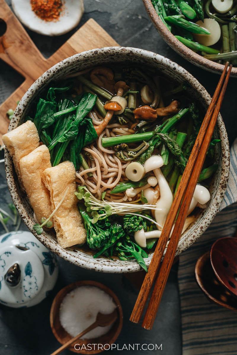 A bowl of vegan sansai soba noodle soup with crispy tofu