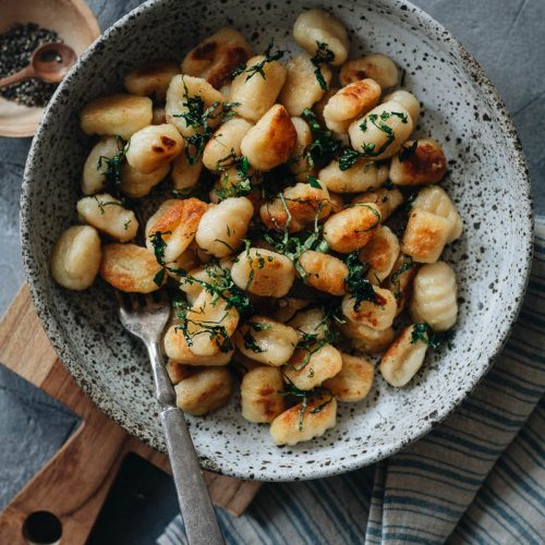 A bowl of homemade potato gnocchi sauteed with herbs