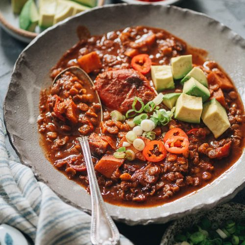 A bowl of vegan sweet potato lentil chili with avocado chunks