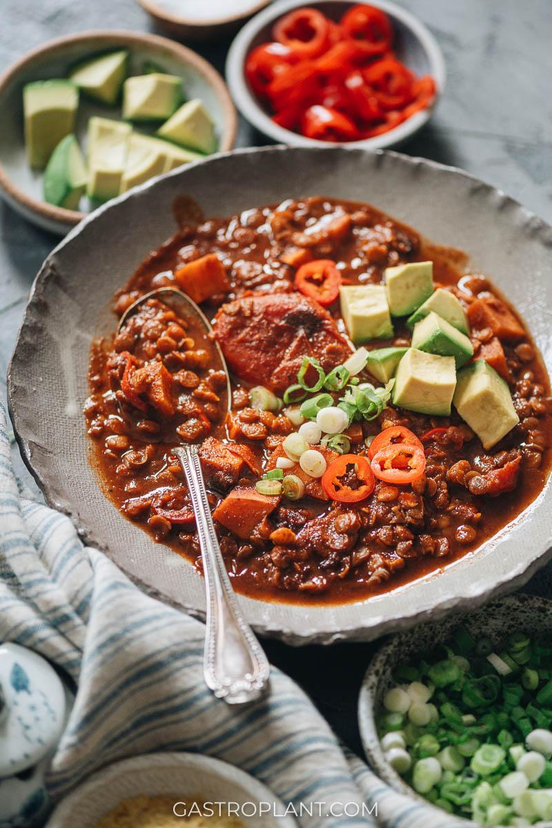 A bowl of vegan sweet potato lentil chili with avocado chunks