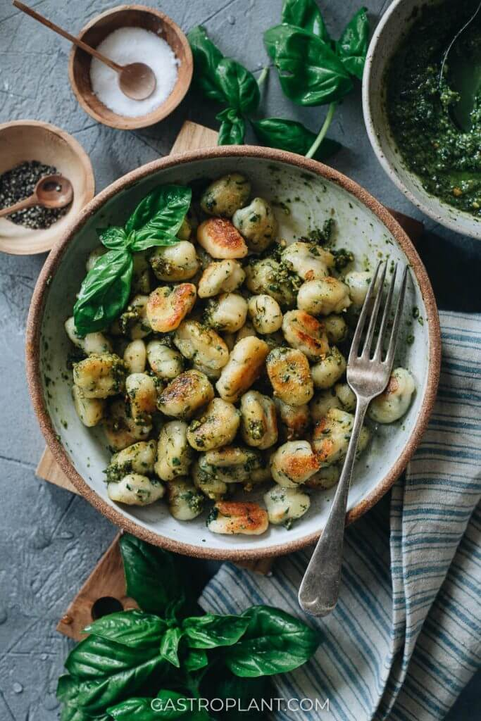 A bowl of homemade potato gnocchi coated in homemade basil pesto sauce