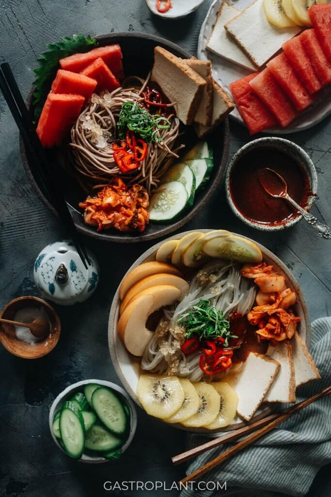 Two bowls of Korean vegan chilled noodles (mul naengmyeon) with watermelon, kimchi, kiwi, and tofu