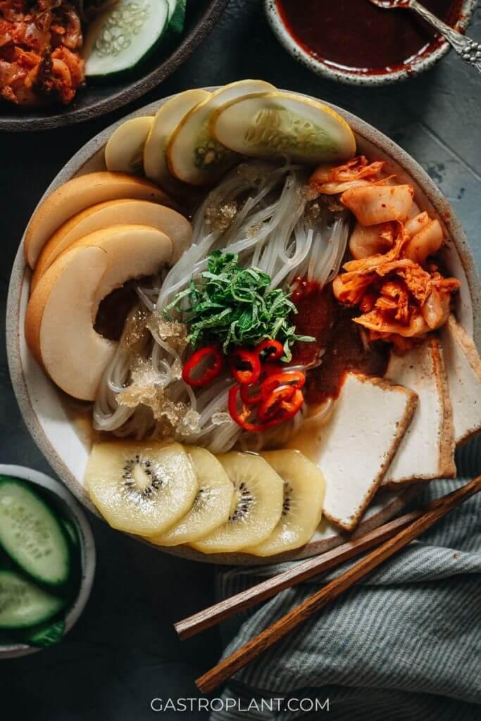 Vegan Korean cold noodles with kimchi, Asian pear, kiwi and tofu