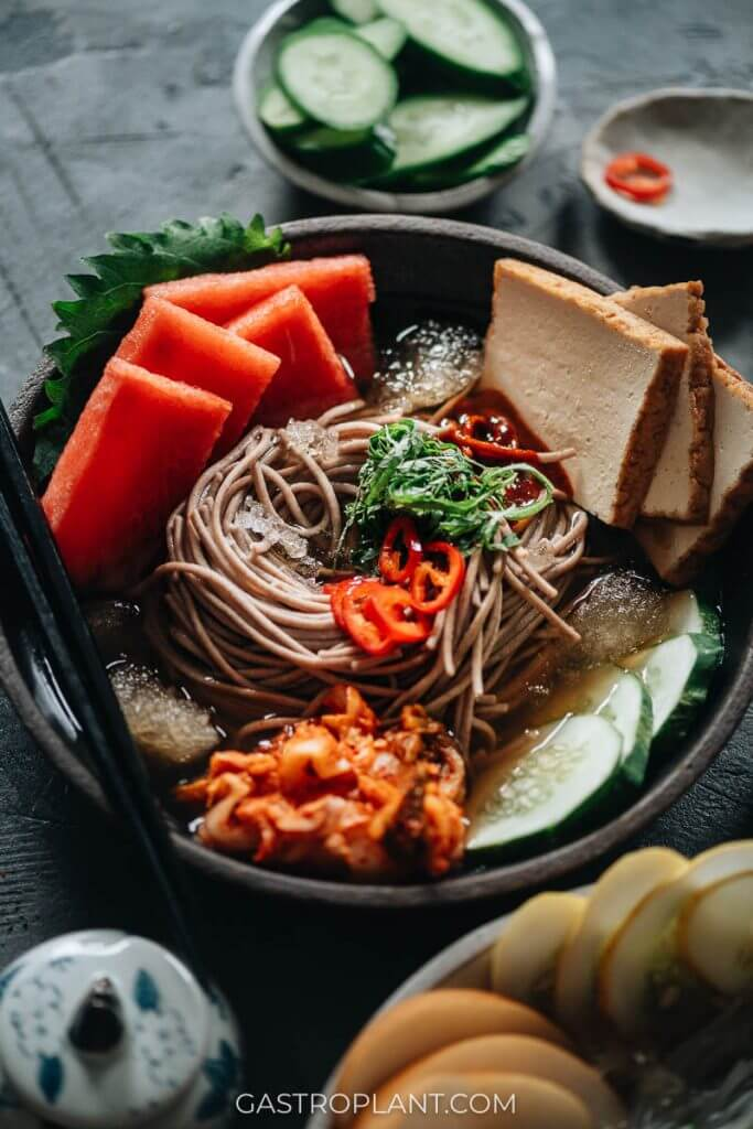 Icy refreshing Korean soba noodles with watermelon, cucumber, kimchi, and tofu with spicy gochujang sauce (mul naengmyeon)