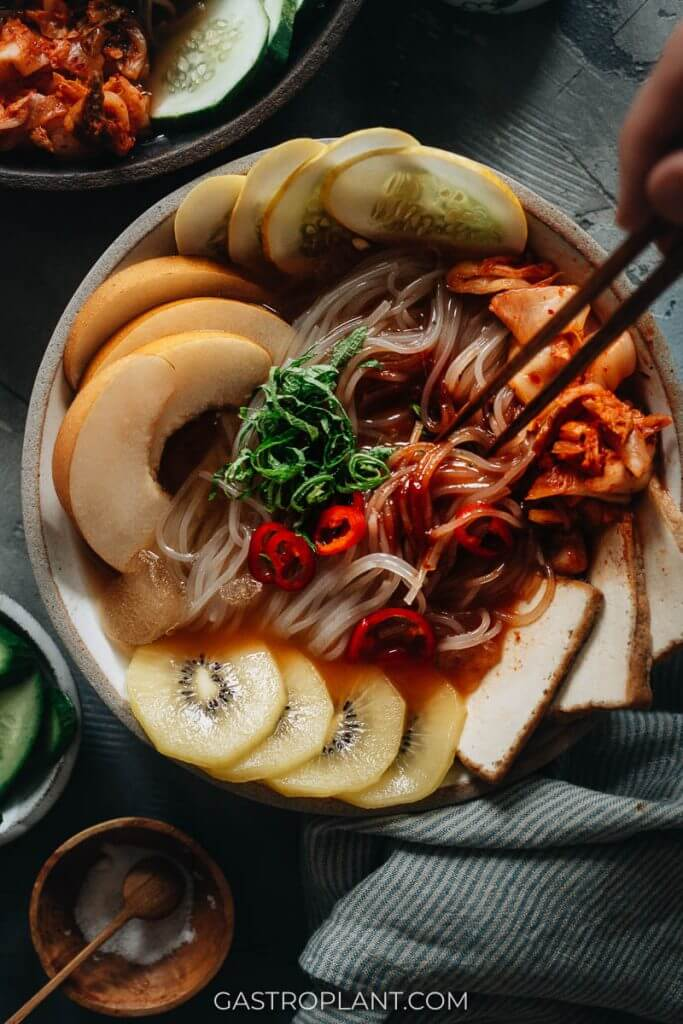 Korean cold noodles (mul naengmyeon) with kiwi, Asian pear, and kimchi in sweet sour spicy broth