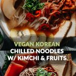 Refreshing Korean chilled spicy sweet noodle soup with kimchi and fruits (vegan)